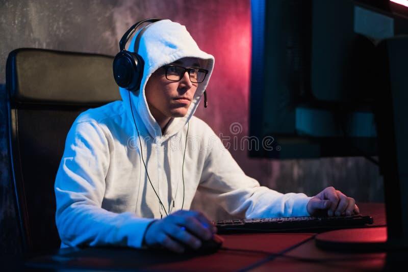 Videojugador encapuchado masculino que juega al juego online en el ordenador de la PC foto de archivo libre de regalías