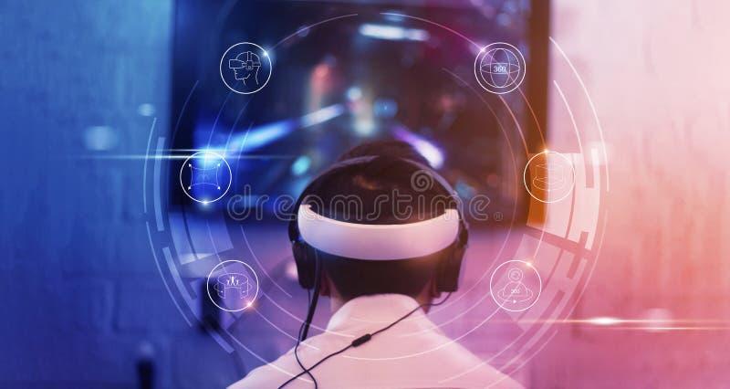 Videojugador joven que lleva gafas y auriculares de VR con el icono conductor de VR y pistola que juegan y que ganan foto de archivo