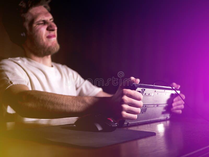 Videojugador loco enojado joven que rompe el teclado que juega a los videojuegos en el ordenador tarde en noche foto de archivo