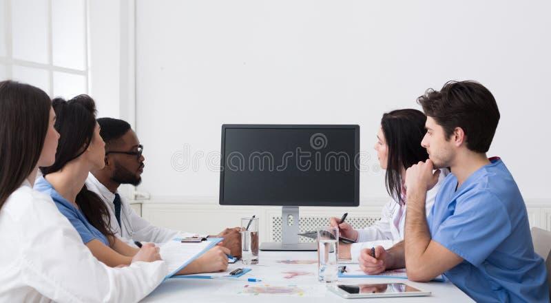 Videokonferenz Team Of Doctors Having Meeting im Krankenhaus lizenzfreie stockbilder
