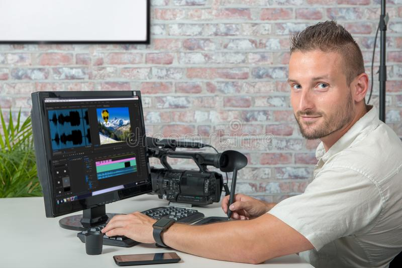 Videoredacteur met computer en professionnalvideocamera stock foto