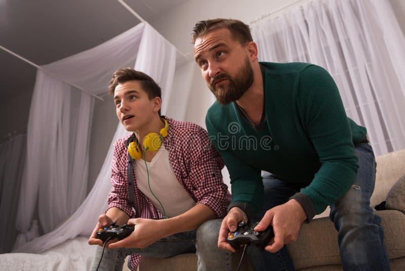 Videospelbegrepp, fader och son som tycker om spela konsolen tillsammans arkivbilder