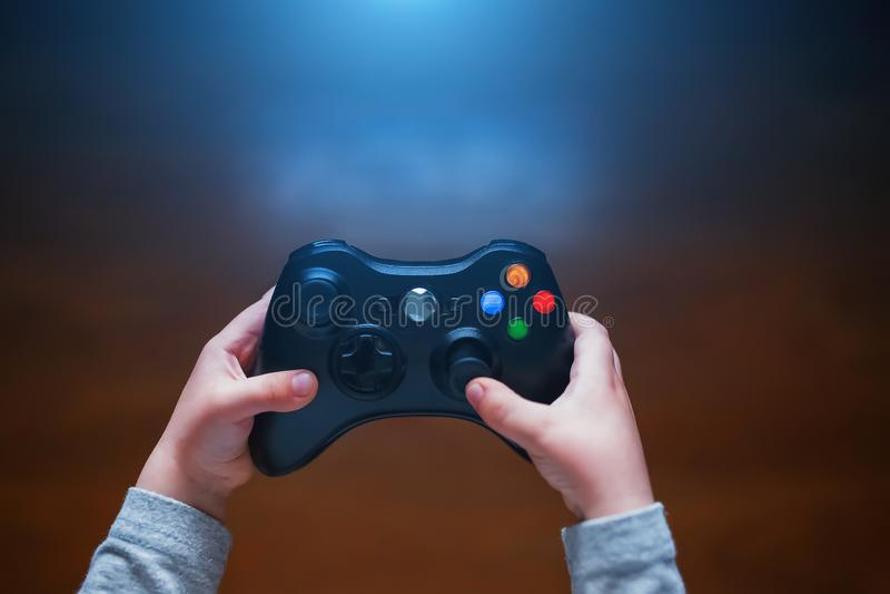 Videospelkontrollant i barns händer, framme av TV:N arkivbilder