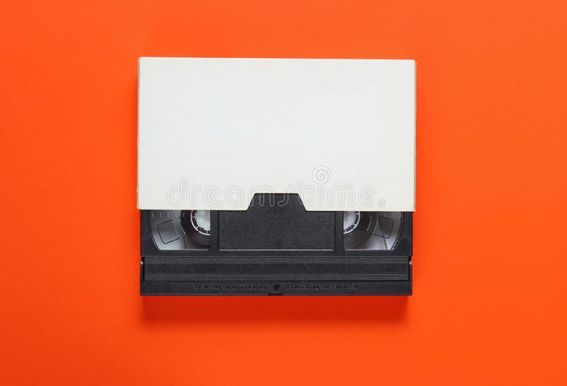 The videotape in a paper case. On orange background. Pop culture attributes, minimalism. Top view royalty free stock images