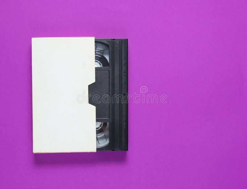 The videotape in a paper case. On purple background. Pop culture attributes, minimalism. Top view royalty free stock photos