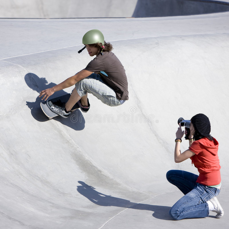 Videotaping skateboard action. Boy does tricks at the skateboard park as girl videotapes royalty free stock image