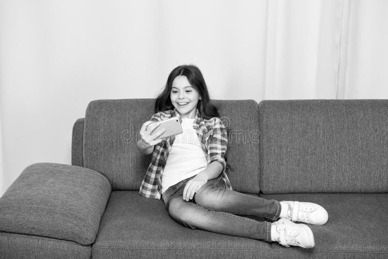 Videovraagconcept Kind het ontspannen op laag en communiceert online Smartphone die van de meisjesgreep selfie nemen Selfie voor stock afbeeldingen