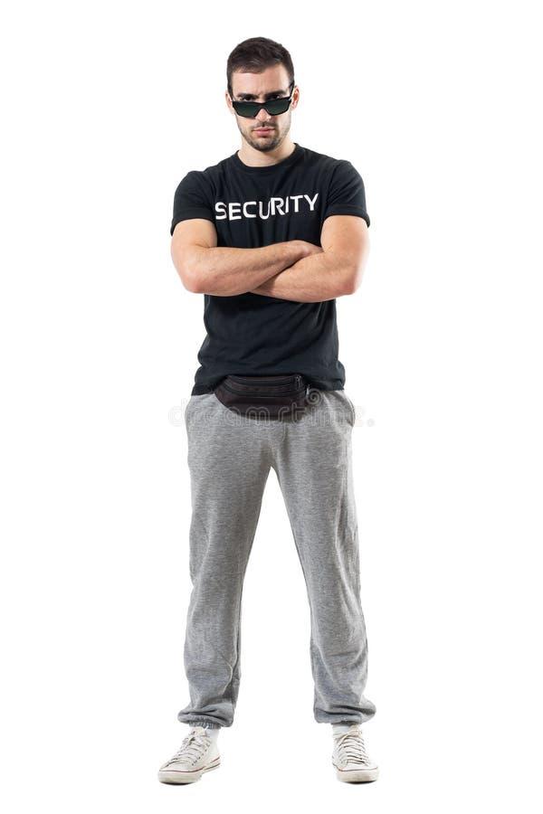 Videur ou garde du corps sérieux dur avec les bras croisés regardant fixement l'appareil-photo images stock