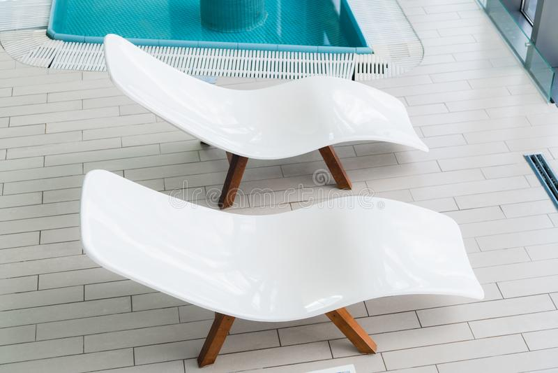 Videz deux chaises longues blanches à l'intérieur de pièce carrelée près de la piscine Personne dans la chambre de station therma photo libre de droits