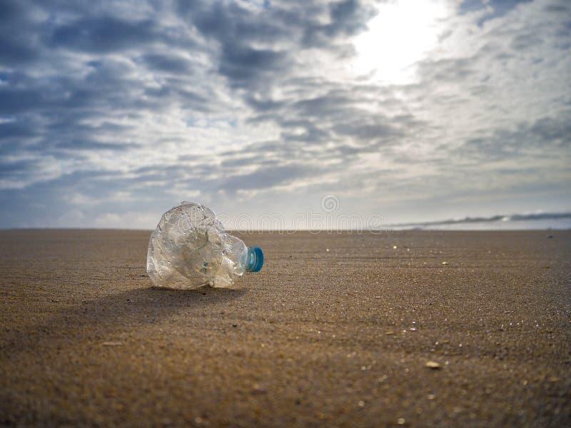 Videz la bouteille en plastique chiffonnée de l'eau abandonnée sur la plage au coucher du soleil images libres de droits