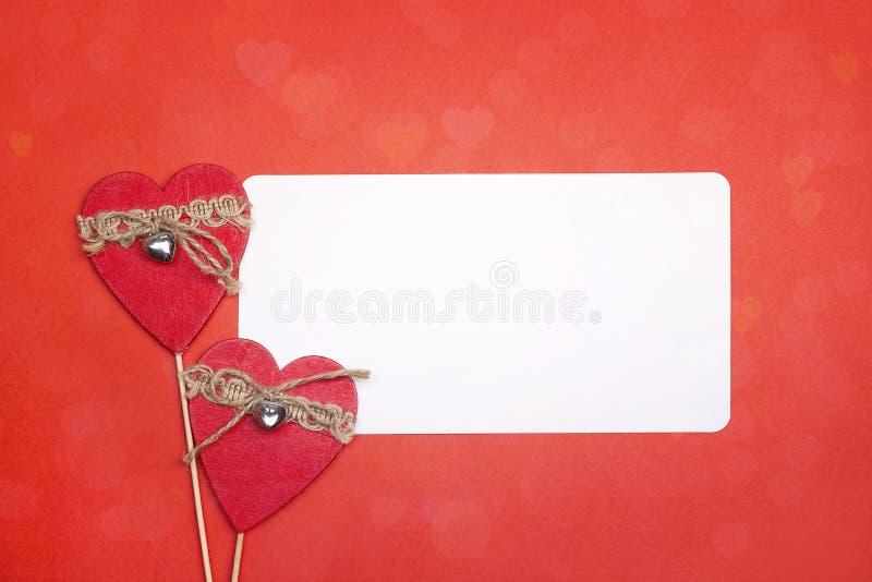 Videz la carte de papier avec les coeurs décoratifs sur le fond rouge image stock