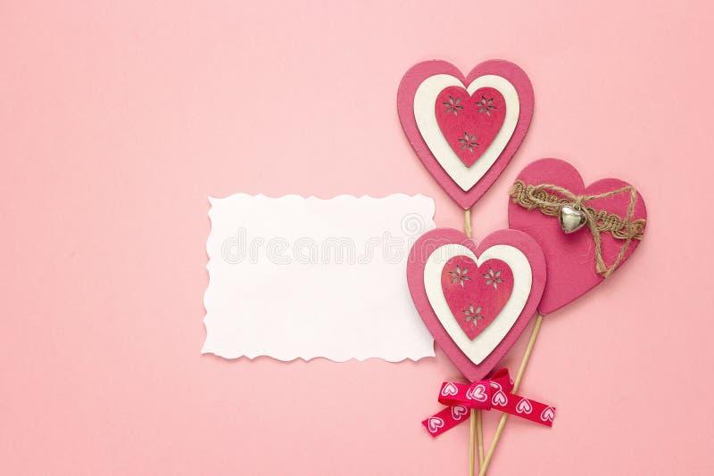 Videz la carte de papier avec les coeurs décoratifs sur un fond rose photos stock
