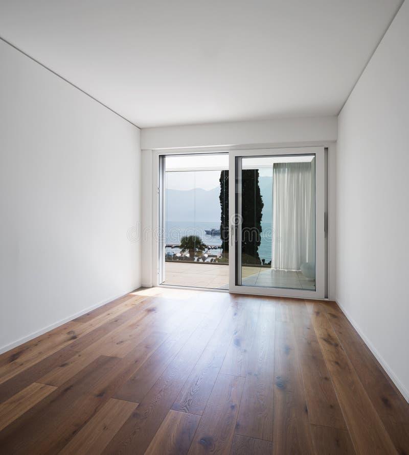 Videz la pièce blanche avec le parquet sombre, qualité images stock