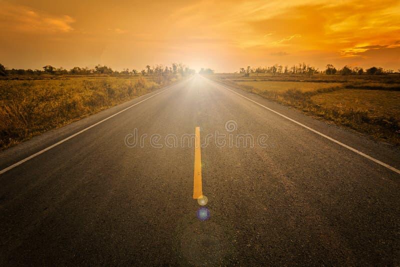 Videz la route goudronnée de tache floue et la lumière du soleil et le signe qui succe de symbole images libres de droits