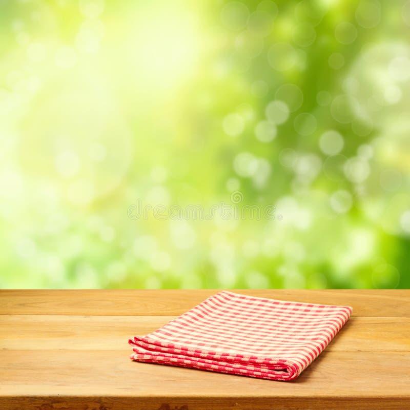 Videz la table en bois avec la nappe au-dessus du fond de bokeh de jardin images libres de droits
