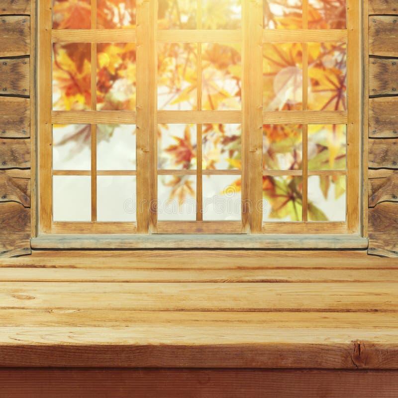 Videz la table en bois de plate-forme au-dessus du fond de bokeh de feuilles de wndow et d'automne image stock