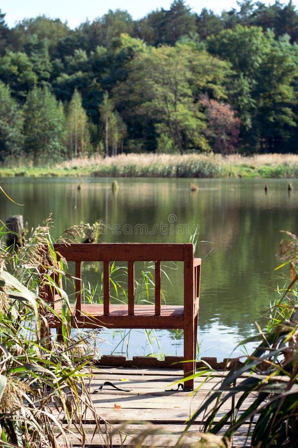 Videz le banc avec vue sur le lac dans la forêt, commencer de l'automne images stock