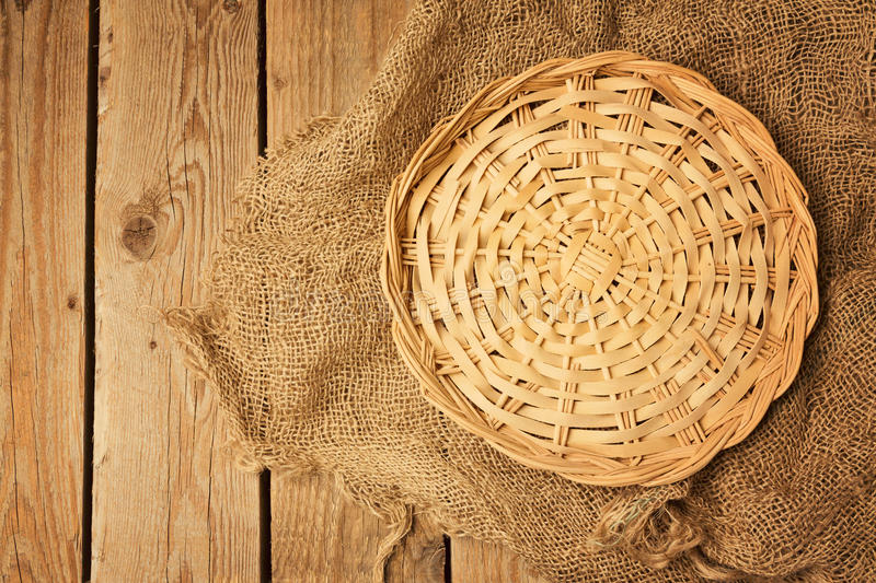Videz le panier en osier sur la toile à sac sur le fond en bois de table photographie stock libre de droits