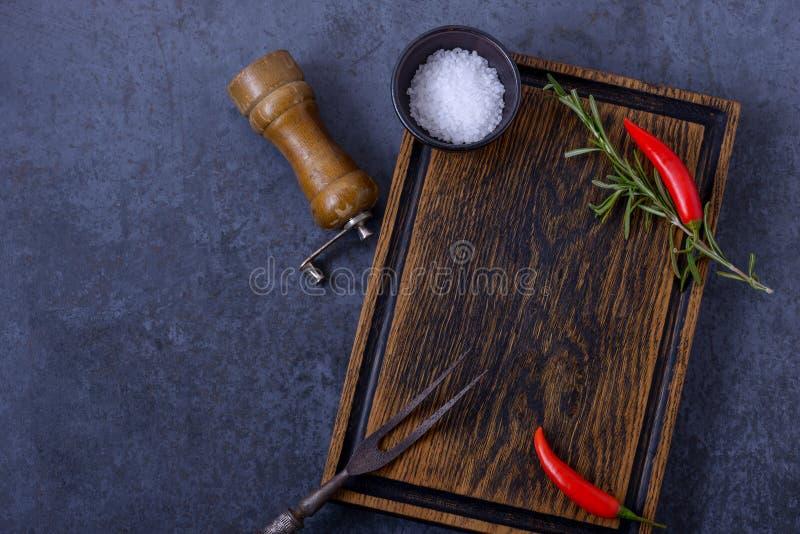Videz le panneau en bois et le poivre de piment, romarin, sel images stock