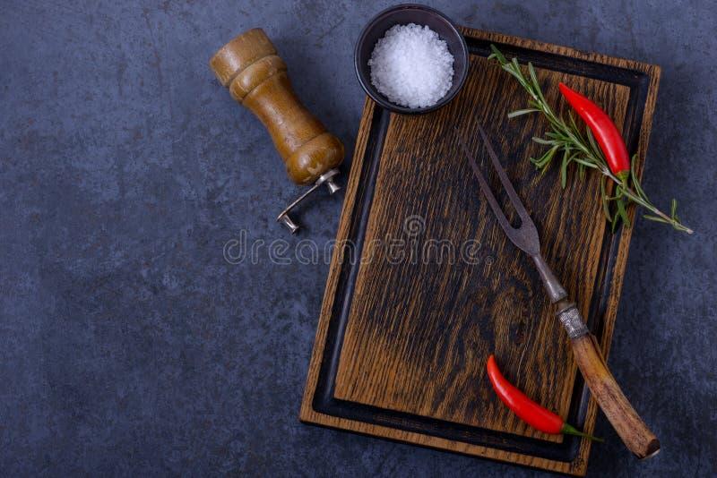 Videz le panneau en bois et le poivre de piment, romarin, sel image libre de droits