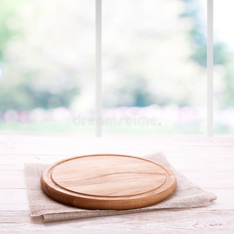 Videz le panneau en bois texturisé de pizza avec la serviette sur le fond brouillé par fenêtre de table et de cuisine photographie stock libre de droits