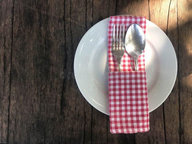 Videz le plat blanc avec l'argenterie, la cuillère et la fourchette et le scoth rouge images libres de droits