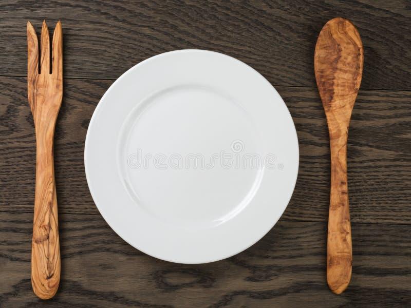 Videz le plat blanc avec la fourchette en bois et la cuillère sur la table de chêne photographie stock
