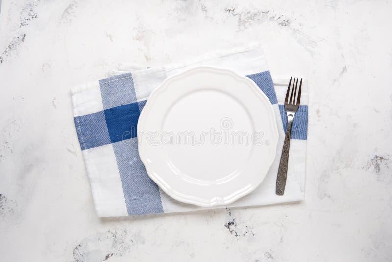 Videz le plat blanc et bifurquez sur une table, vue supérieure images stock