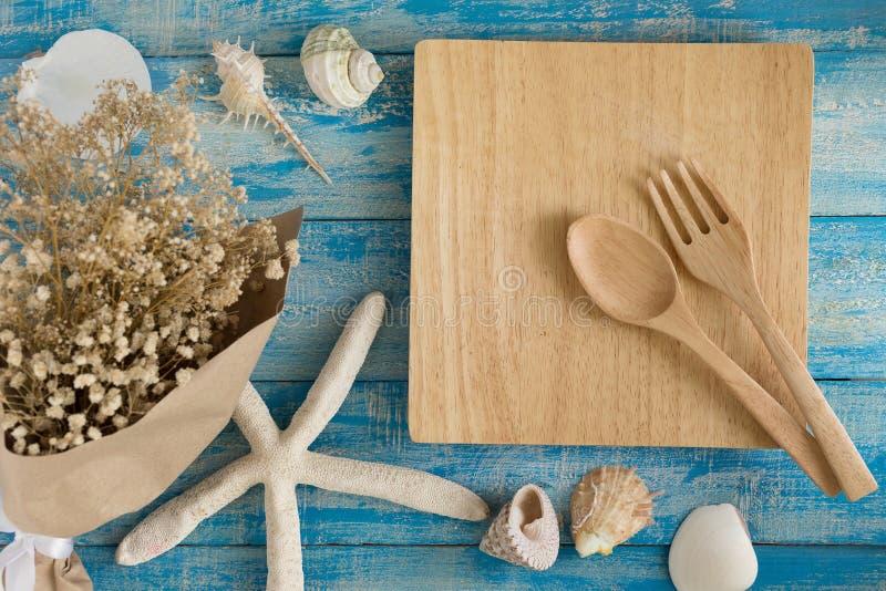 Videz le plat et les coquilles et les étoiles de mer en bois de mer sur un bleu rustique photographie stock