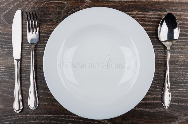 Videz le plat, le couteau, la fourchette et la cuillère blancs sur la table image libre de droits