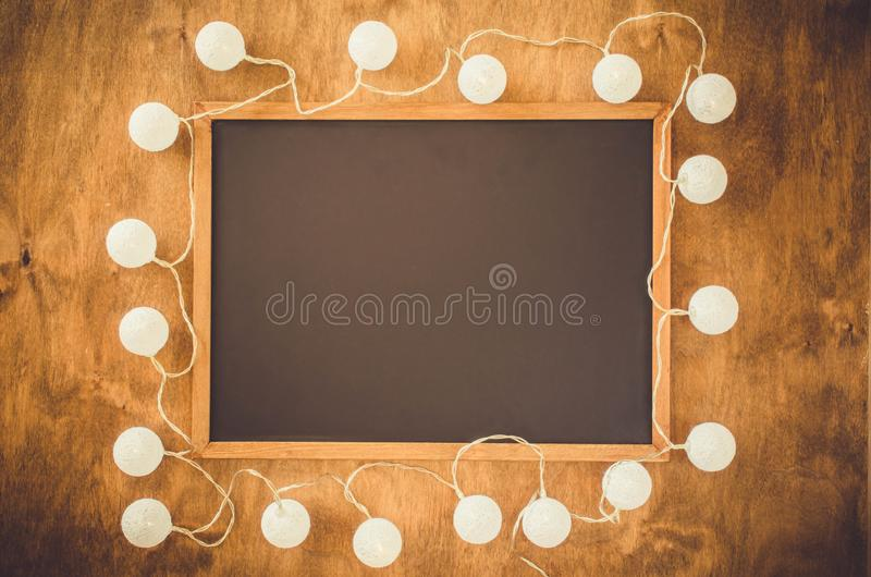 Videz le tableau noir entouré avec les lumières décoratives blanches sur le fond en bois photographie stock