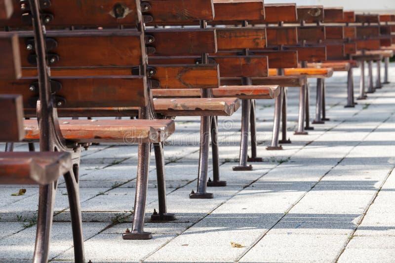 Videz les bancs en bois dans une rangée, air ouvert image stock