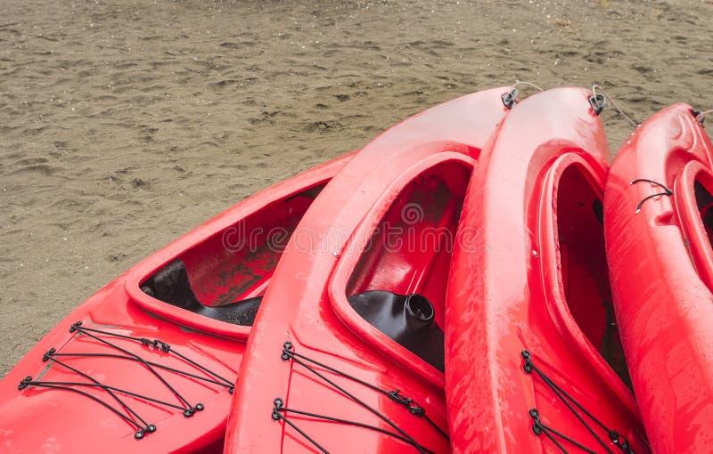 Videz les kayaks récréationnels en plastique rouges pour le loyer ou la location, stockés sur la plage sablonneuse après des heur image libre de droits