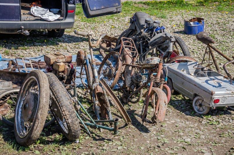 Videz les vieux bicyclettes, motos, voitures de jouet, moteurs, pneus et roues rouillés cassés avec des rais en plein air au sol photo stock