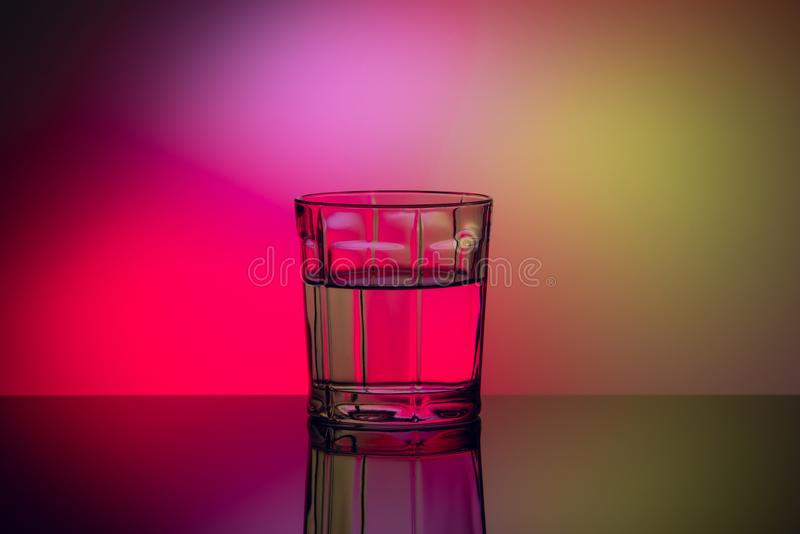Vidrio abstracto con el líquido en fondo multicolor imágenes de archivo libres de regalías