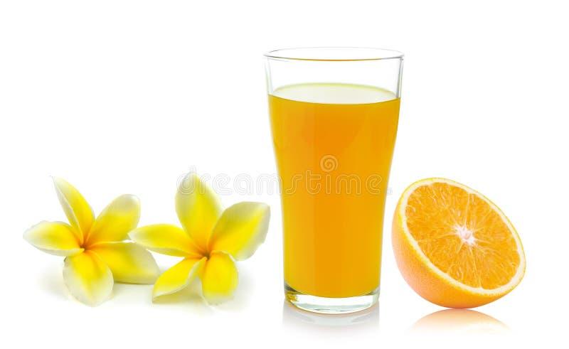vidrio anaranjado con el jugo y la flor del Frangipani fotografía de archivo