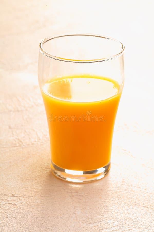 Vidrio bebido mitad de zumo de naranja fresco foto de archivo