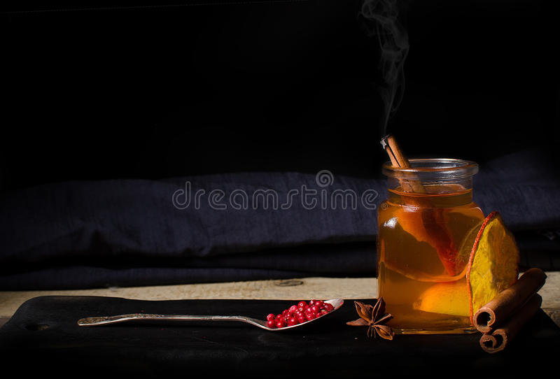 Vidrio caliente de té de la bebida con la naranja y la pimienta imágenes de archivo libres de regalías