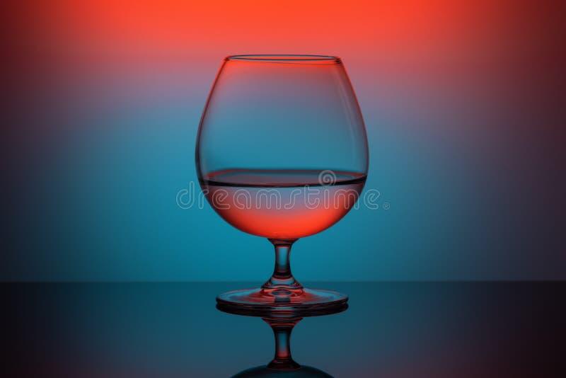 Vidrio coloreado abstracto del coñac en fondo azul anaranjado foto de archivo libre de regalías
