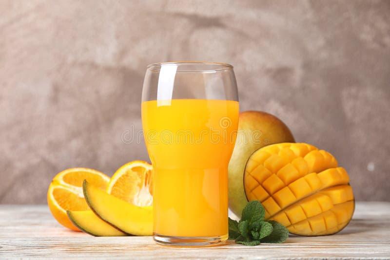 Vidrio con el jugo fresco del mango y las frutas sabrosas en la tabla fotografía de archivo libre de regalías
