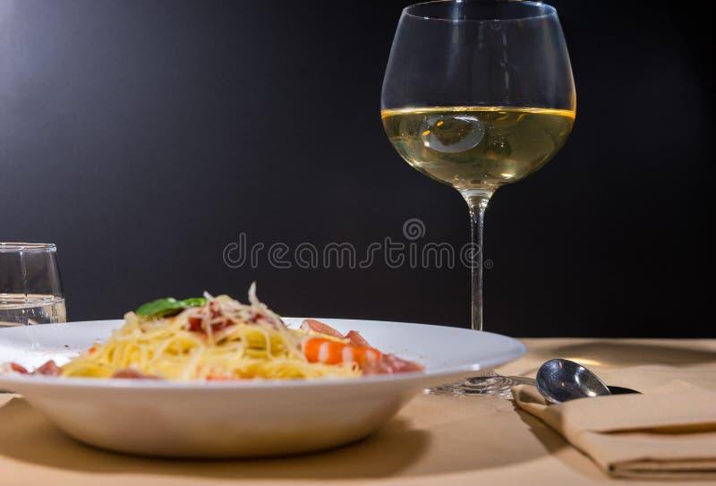 Vidrio con el vino cerca de las pastas deliciosas con los camarones, gra de los espaguetis imágenes de archivo libres de regalías