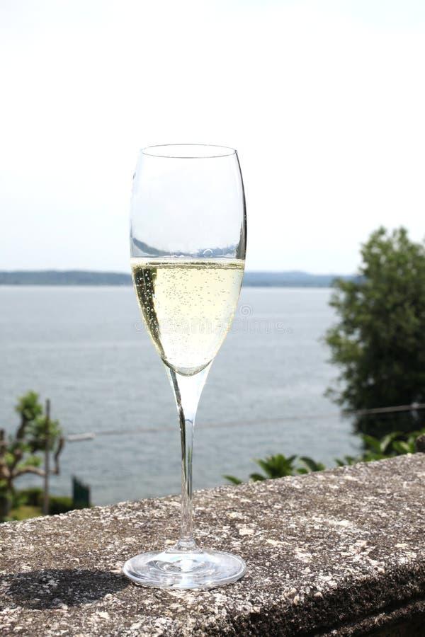 Vidrio con el vino del champán en una barandilla de piedra foto de archivo