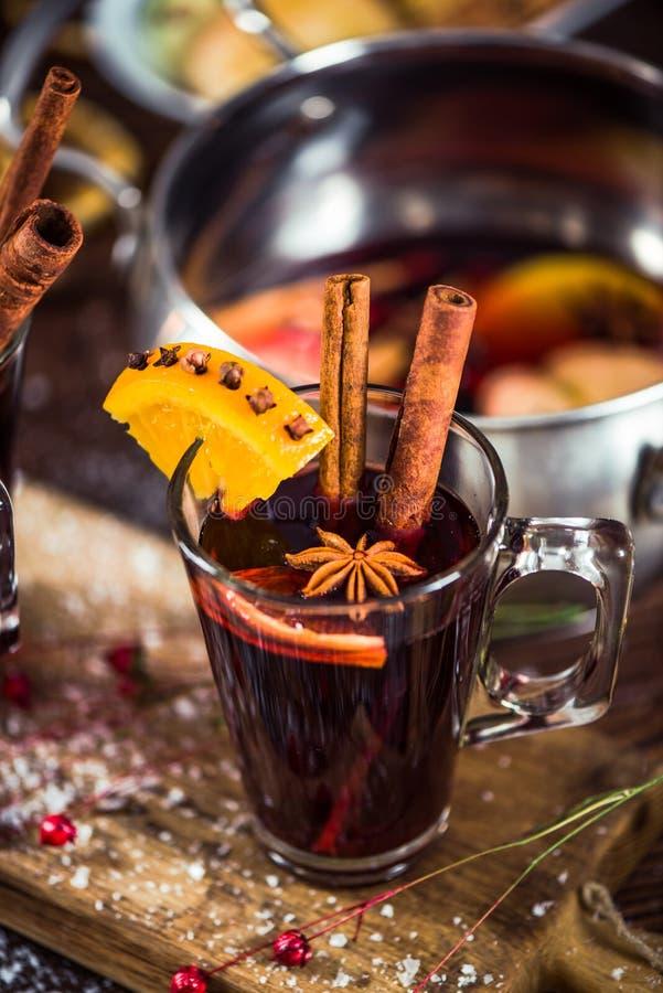 Vidrio con el vino reflexionado sobre con las especias para waming el días de invierno foto de archivo