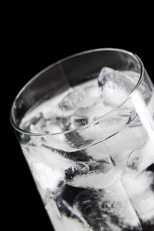 Vidrio con hielo en negro foto de archivo