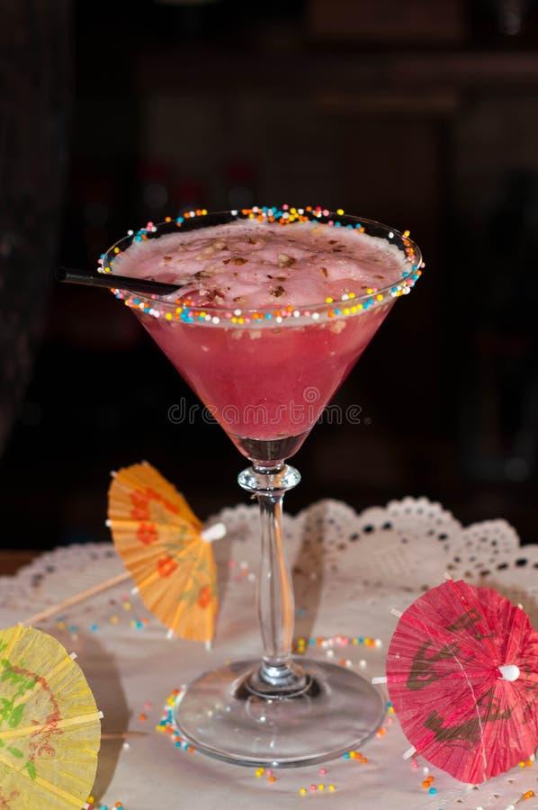 Vidrio con la bebida rosada del alcohol y paja en servilleta del Libro Blanco con los paraguas del ocktail del  de Ñ imagenes de archivo