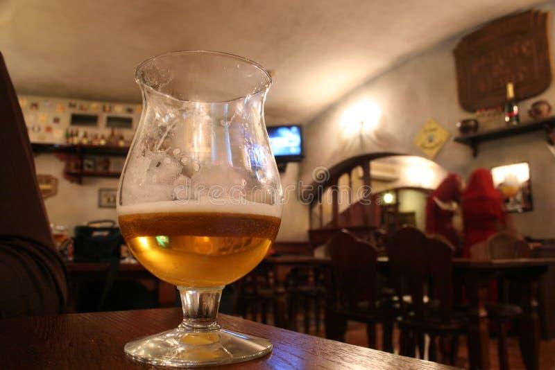 Vidrio con la cerveza en barra foto de archivo