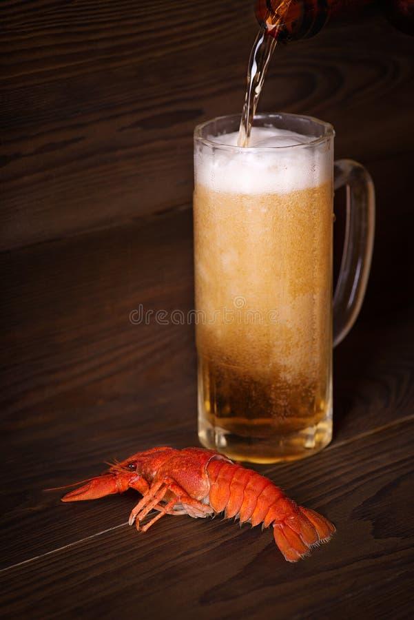 Vidrio con la cerveza y un cangrejo hervido en una tabla de madera imagen de archivo