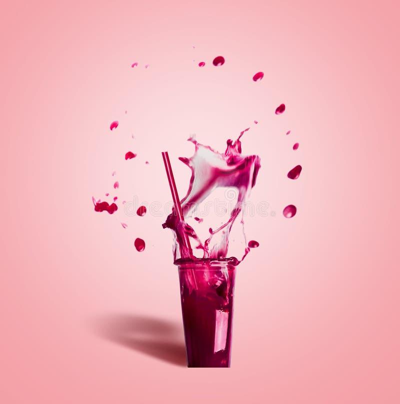 Vidrio con la paja de beber y la bebida púrpura del verano del chapoteo: smoothie o jugo en rosa foto de archivo