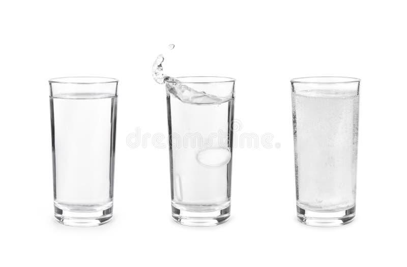 Vidrio con la tableta efervescente en agua con las burbujas en los vagos blancos imagen de archivo
