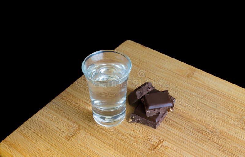 Vidrio con la vodka y el chocolate en la tabla de madera y el fondo negro imagen de archivo